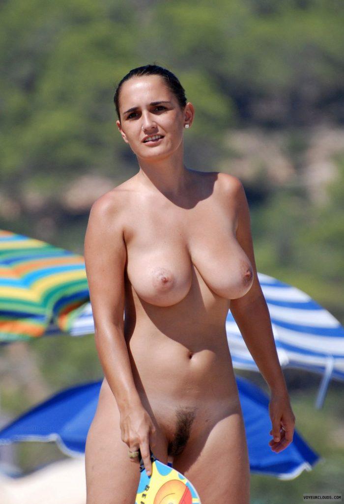 Nudista en la playa jugando